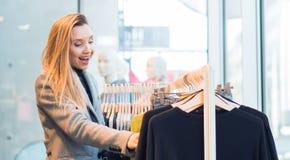 Mujer joven sorprendida que hace compras en la tienda, colocándose delante de la ropa fotos de archivo libres de regalías