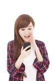 Mujer joven sorprendida que mira el teléfono elegante Fotografía de archivo libre de regalías