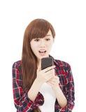 Mujer joven sorprendida que mira el teléfono elegante Foto de archivo libre de regalías