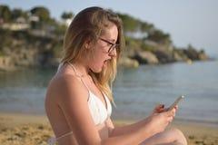 Mujer joven sorprendida que mira su teléfono móvil en la playa fotos de archivo