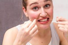 Mujer joven sorprendida que muele sus dientes al usar la seda dental Imagen de archivo