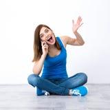 Mujer joven sorprendida que se sienta en el piso Foto de archivo
