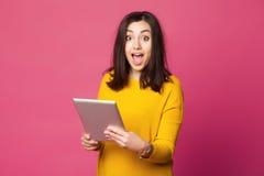 Mujer joven sorprendida que sostiene la tableta Foto de archivo libre de regalías