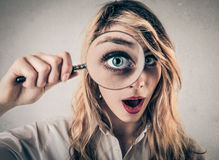 Mujer joven sorprendida que usa una lente de la mano fotografía de archivo