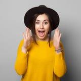 Mujer joven sorprendida sobre fondo gris Foto de archivo