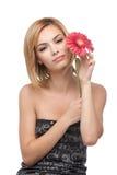 Mujer joven, sosteniendo una flor cerca de su cara Fotografía de archivo