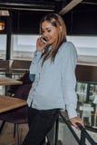 Mujer joven stading y que habla en el teléfono en café foto de archivo