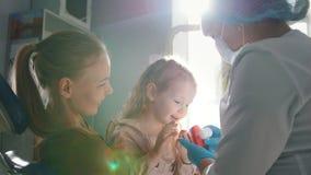 Mujer joven, su hija y dentista en una oficina dental, un stomatologist que dice cómo cuidar para los dientes almacen de metraje de vídeo