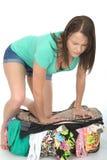 Mujer joven subrayada frustrada que intenta cerrar una maleta que desborda que mira a Fed Up Fotos de archivo