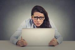 Mujer joven subrayada que mira el ordenador Imagen de archivo libre de regalías