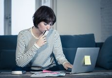Mujer joven subrayada y abrumada que paga deudas y cuentas de la tarjeta de crédito en el ordenador portátil fotografía de archivo