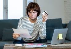 Mujer joven subrayada y abrumada que paga deudas y cuentas de la tarjeta de crédito en el ordenador portátil fotos de archivo libres de regalías