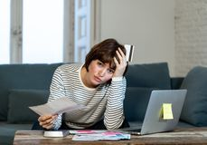 Mujer joven subrayada y abrumada que paga deudas y cuentas de la tarjeta de crédito en el ordenador portátil fotografía de archivo libre de regalías