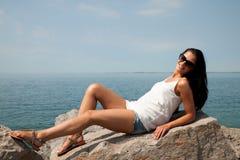 Mujer joven suntaning en piedras en la playa Fotos de archivo libres de regalías