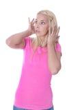 Mujer joven temerosa en la camisa rosada aislada sobre blanco Foto de archivo