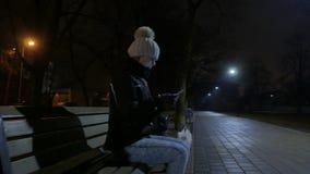 Mujer joven texting en el teléfono celular Calle 4K UHD de la noche almacen de video