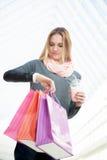 Mujer joven a toda prisa que comprueba tiempo después de hacer compras Foto de archivo