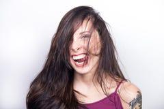Mujer joven torpe que hace la cara tonta que pega la lengua hacia fuera y Laug Foto de archivo libre de regalías