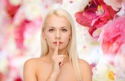Mujer joven tranquila con el finger en los labios Fotografía de archivo libre de regalías