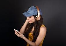 Mujer joven tranquila hermosa en casquillo azul que escucha la música en los wi Foto de archivo libre de regalías