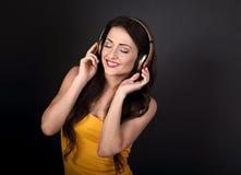 Mujer joven tranquila hermosa en el top del amarillo que escucha la música adentro Fotos de archivo libres de regalías