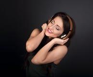 Mujer joven tranquila hermosa que escucha la música en headp inalámbrico Imagen de archivo