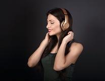 Mujer joven tranquila hermosa que escucha la música en headp inalámbrico Fotos de archivo libres de regalías