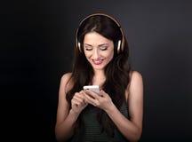 Mujer joven tranquila hermosa que escucha la música en headp inalámbrico Fotos de archivo