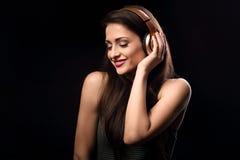 Mujer joven tranquila hermosa que escucha la música en headp inalámbrico Fotografía de archivo