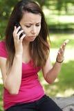 Mujer joven trastornada en el teléfono Foto de archivo