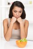 Mujer joven trastornada que guarda dieta y que come verduras Fotos de archivo libres de regalías