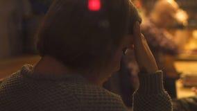 Mujer joven trastornada que piensa en problemas, sentándose solamente en café, crisis de la vida metrajes