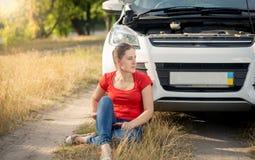 Mujer joven trastornada que se sienta en la tierra y que se inclina en su coche quebrado en el camino del campo Imagenes de archivo