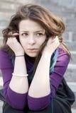 Mujer joven trastornada que se sienta en las escaleras Imágenes de archivo libres de regalías