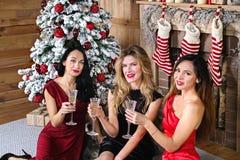 Mujer joven tres con un vidrio de champán que se sienta delante de la chimenea y del árbol del Año Nuevo Foto de archivo