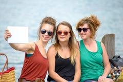 Mujer joven tres en la playa con su tableta digital foto de archivo