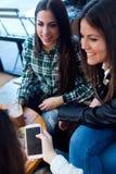 Mujer joven tres que usa el teléfono móvil en la tienda del café Fotografía de archivo