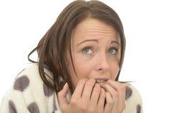 Mujer joven triste ansiosa asustada nerviosa inestable que muerde sus clavos Fotos de archivo libres de regalías