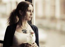 Mujer joven triste con el cóctel que mira hacia fuera la ventana Foto de archivo libre de regalías