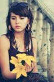 Mujer joven triste con flores en la calle de la ciudad Fotografía de archivo