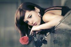 Mujer joven triste con una calle roja de la ciudad de la rosa n Foto de archivo libre de regalías