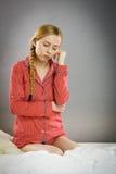 Mujer joven triste del adolescente que se sienta en cama Imágenes de archivo libres de regalías