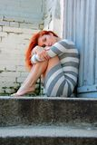 Mujer joven triste en las escaleras Imagen de archivo