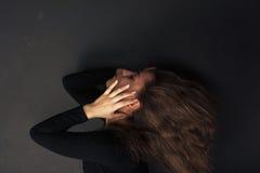 Mujer joven triste hermosa que lleva a cabo las manos en su cara en un fondo oscuro Imágenes de archivo libres de regalías