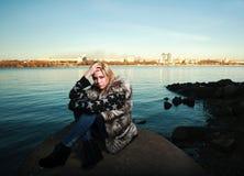 Mujer joven triste hermosa que se sienta al aire libre cerca del río Imagen de archivo libre de regalías