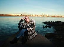 Mujer joven triste hermosa que se sienta al aire libre cerca del río Imagen de archivo