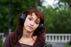 Mujer joven triste que escucha la música. Fotografía de archivo