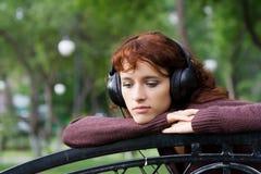 Mujer joven triste que escucha la música. Imagenes de archivo