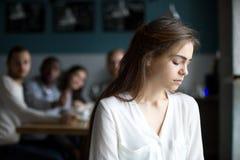 Mujer joven triste que evita a los amigos que sufren del cotilleo o del bul Imagen de archivo