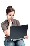 Mujer joven triste que mira en la computadora portátil Imágenes de archivo libres de regalías